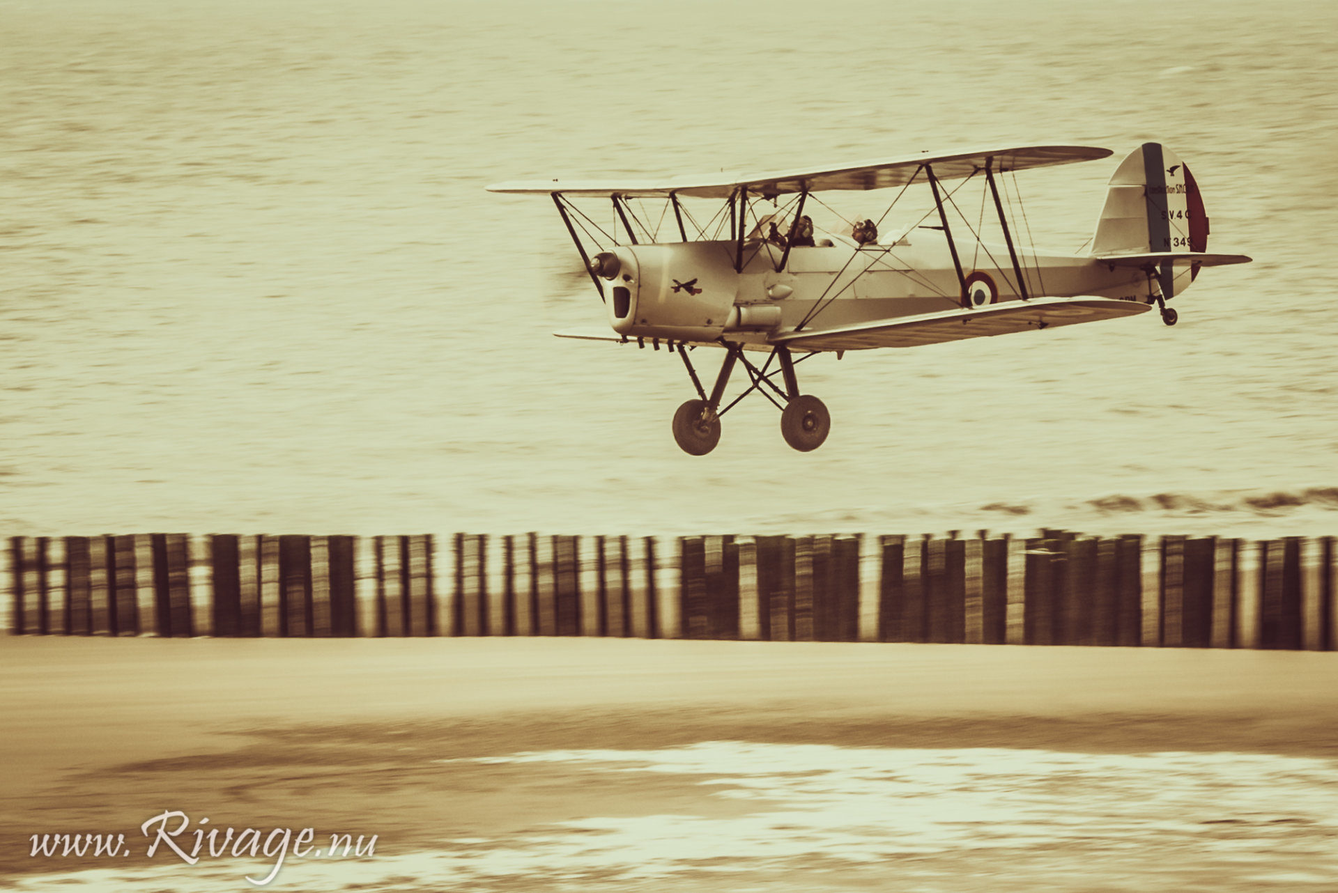 vintage dubbeldekker vliegtuig land op het strand
